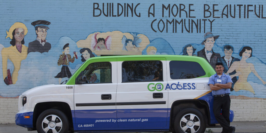 side view of paratransit vehicle in front of blue wall saying building a better community
