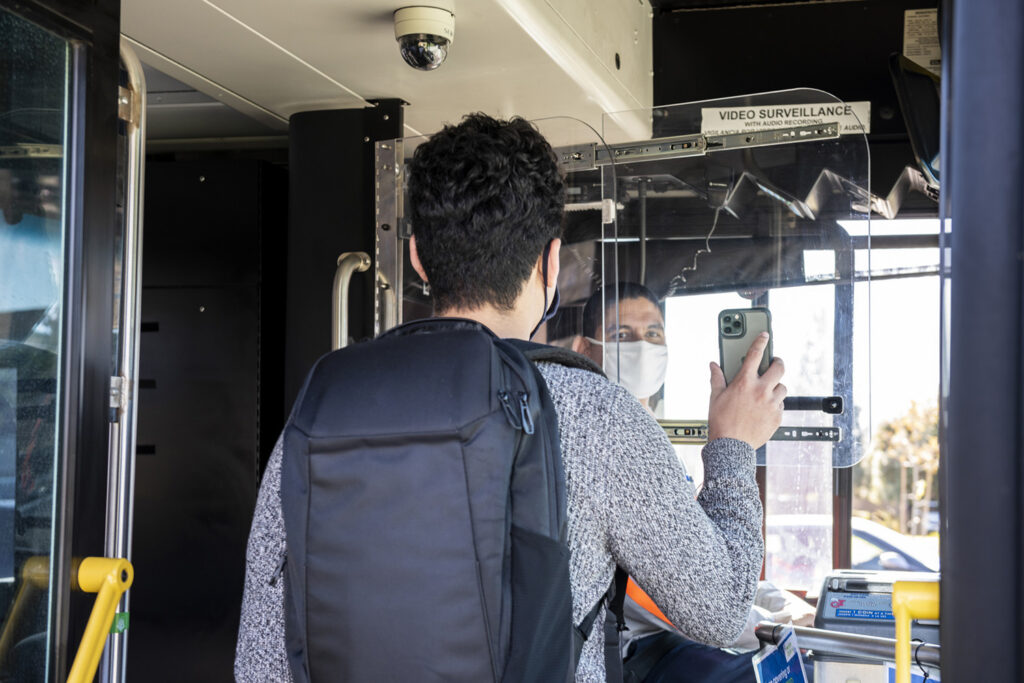 person wearing black backpack holding phone up to driver to show bus pass