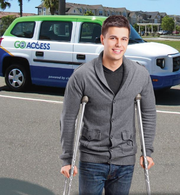 young man on crutches in front of access van