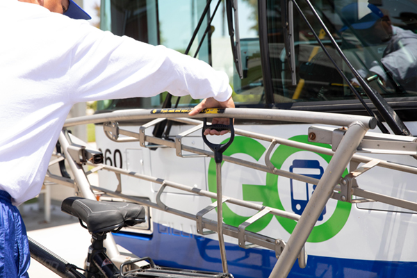 man pulling handle and lifting down the bus bike rack