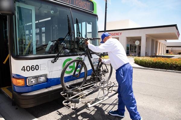 man placing bike on innner rack of bus