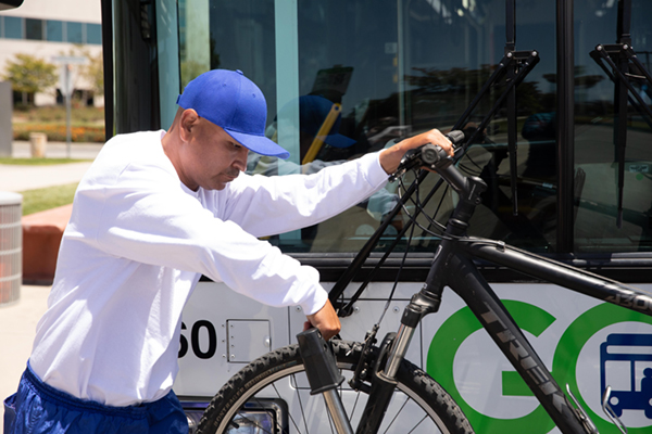 man securing bus bike rack on front tire